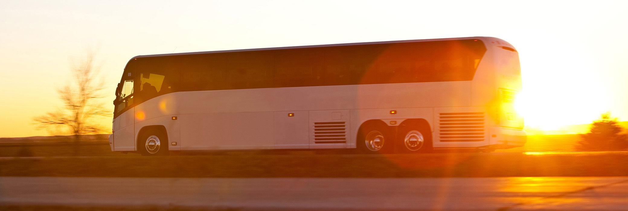 Ein weißer Reisebus, der auf einer Landstraße in den Sonnenuntergang fährt