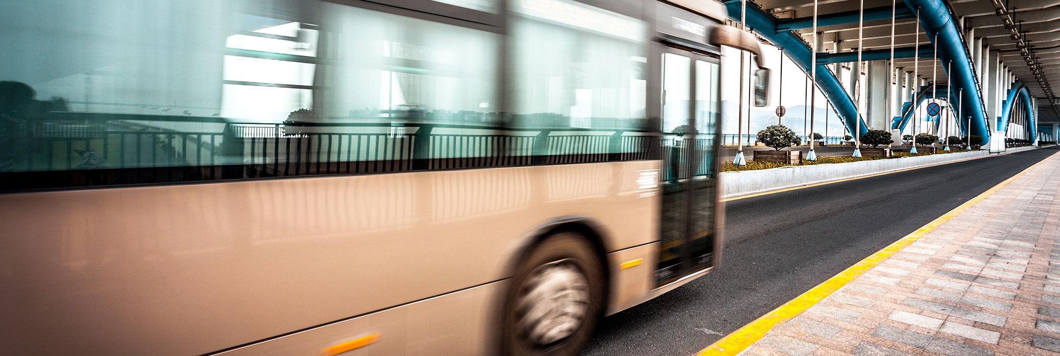 Autobús blanco cruzando un puente con arcos metálicos de color azul y blanco