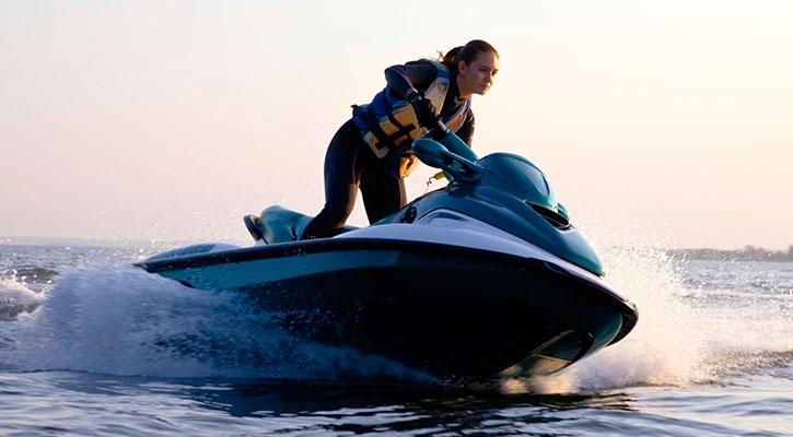 Denizde jetskiyle hız yapıp ıslanan bir adam