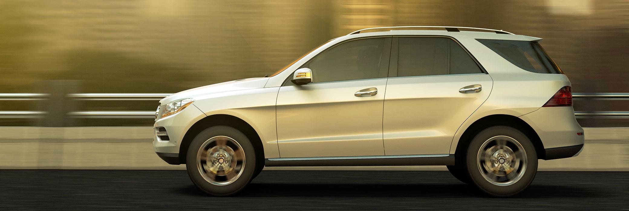 Srebrn srednje velik avtomobil, prikaza od strani, se pelje po cesti