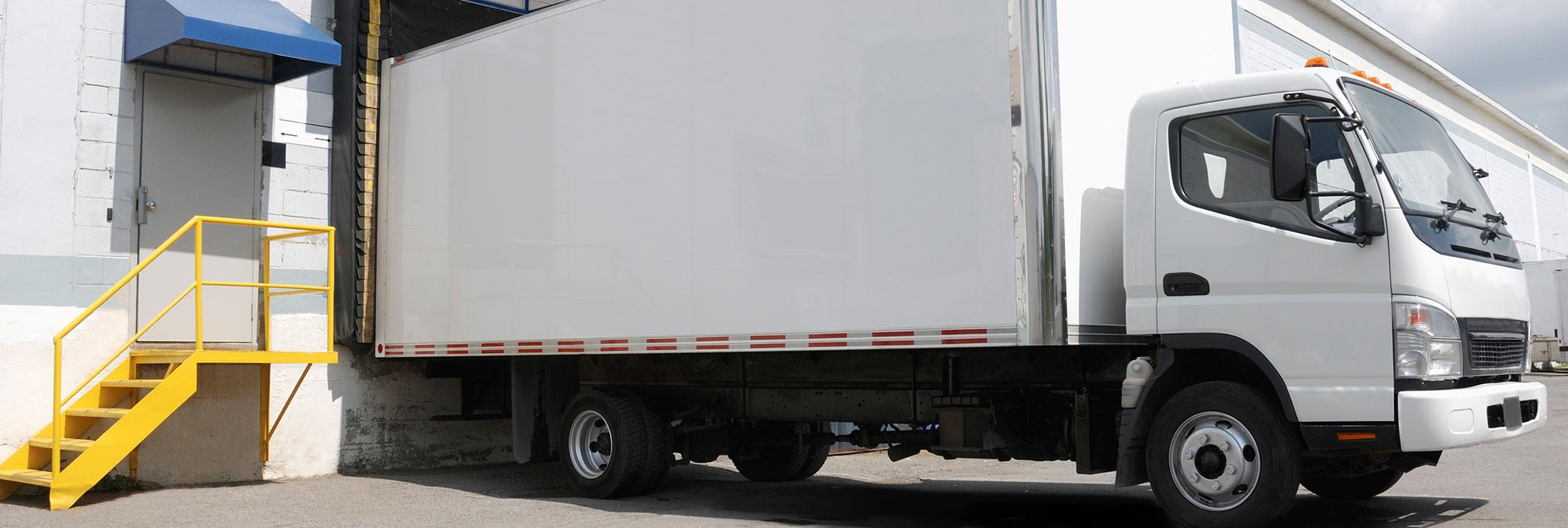 Vehículo de reparto blanco detenido delante de un edificio para recibir la carga