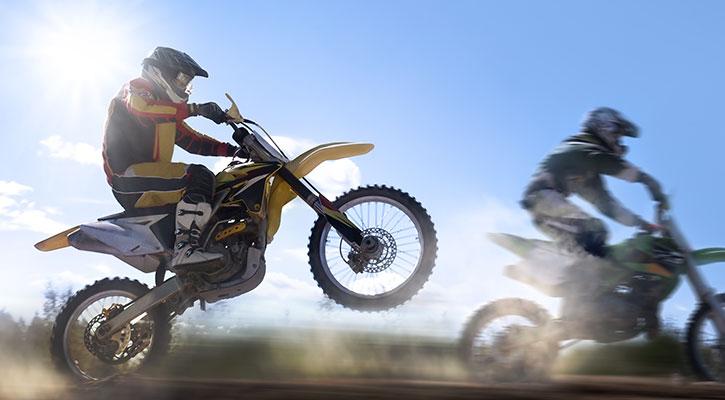 Två personer kör en motorcykel på en landsväg
