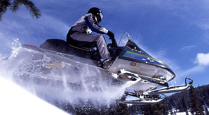 En person flyger över en kulle med sin snöskoter, blå himmel i bakgrunden