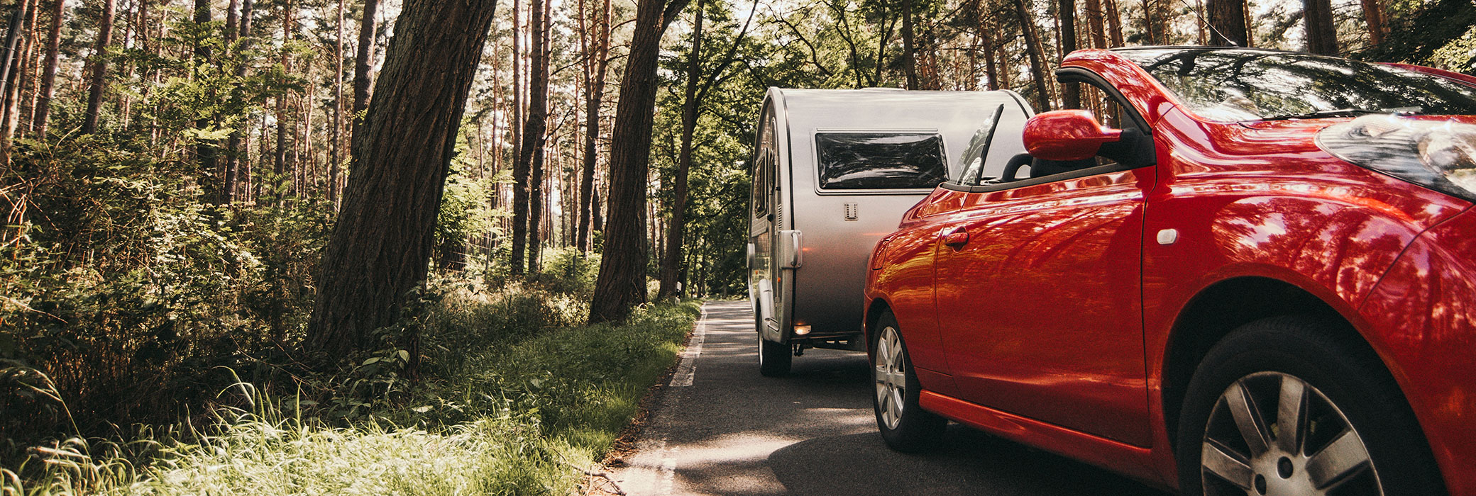Red cabriolet with a white caravan driving down a country road
