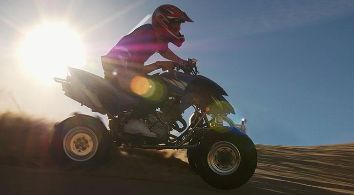 En kille har roligt körandes en fyrhjuling på en väg