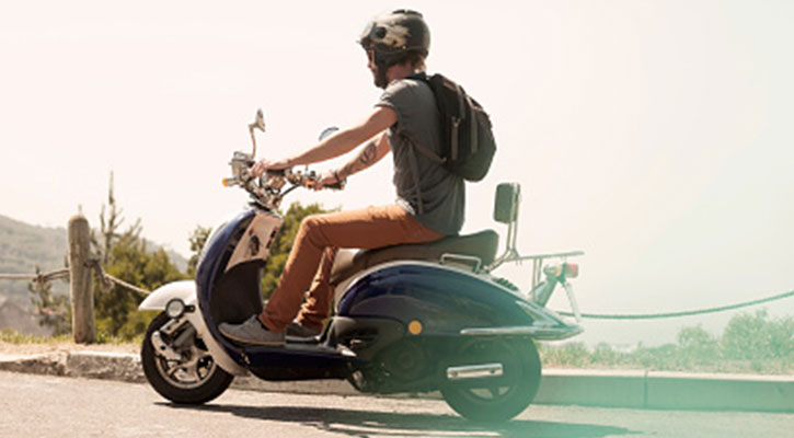 En kille kör iväg på en scooter