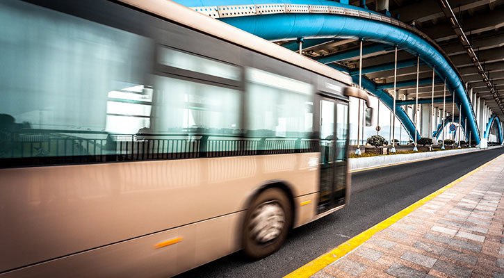White bus driving on a bridge with blue and white metal arches
