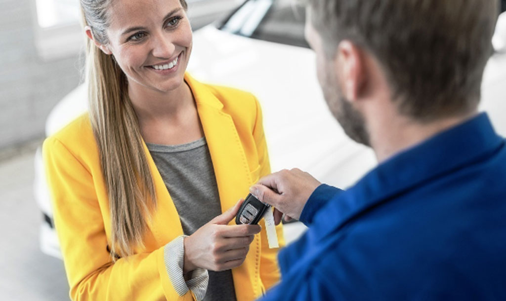 Customer (woman) in yellow coat handing retailer (man) the keys to her car
